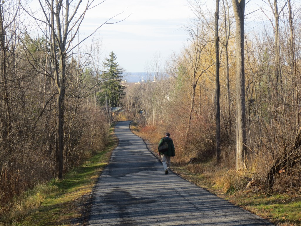A hiker walks a portion of the East Ithaca Recreation Way on the side of Snyder Hill, not far from Cornell University.
