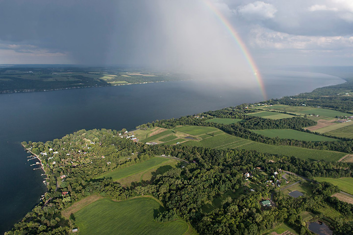 Aerial photograph by Bill Hecht of a rainbow over Cayuga Lake by Sheldrake Point