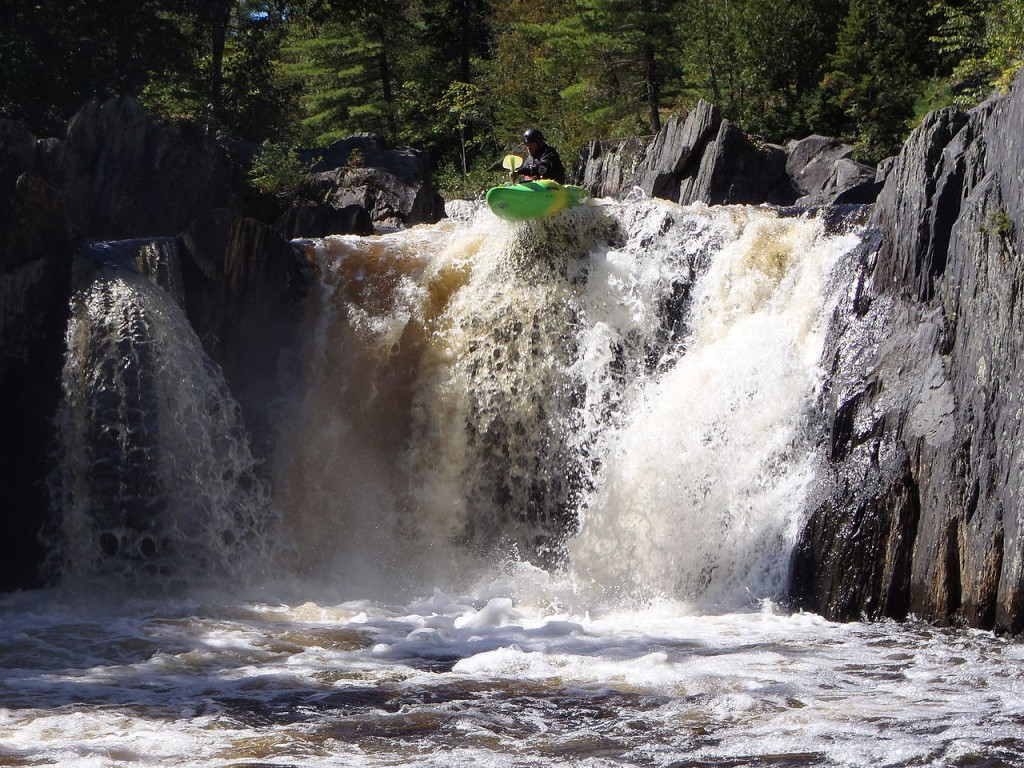 """A kayaker portaging the rapid 'Wedge'"" Wikimedia"