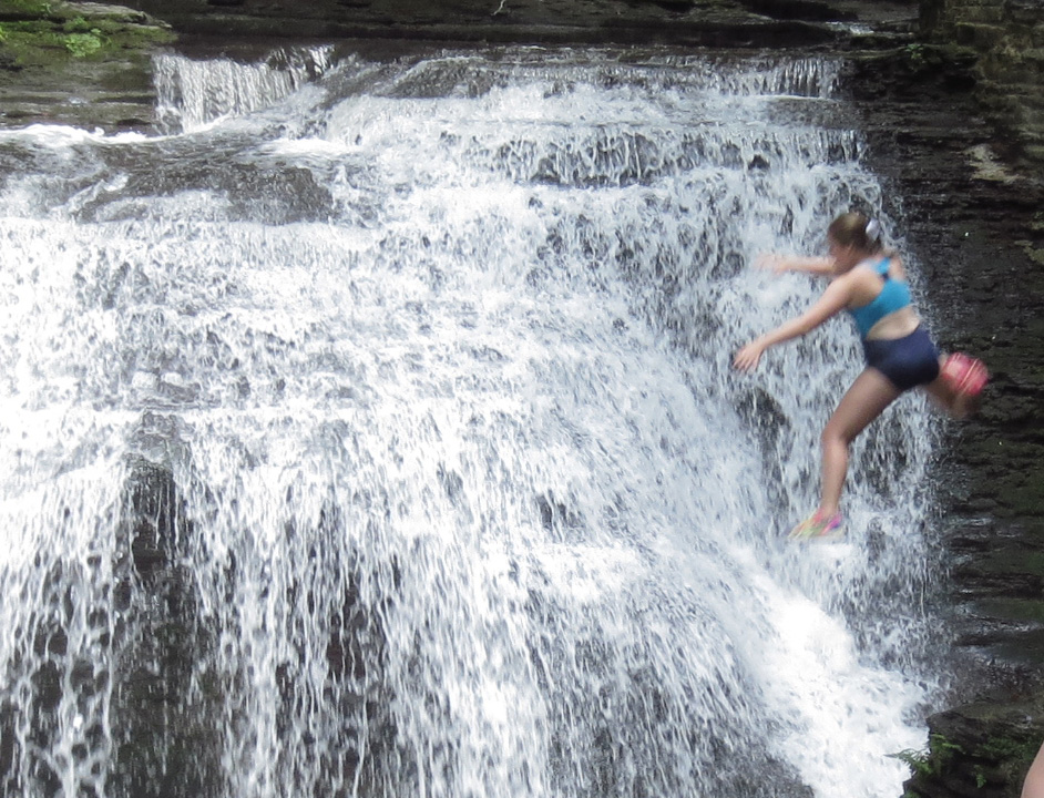 A young woman jumps from the trail into a deep pool in the gorge at Buttermilk Falls State Park. This is dangerous and illegal.